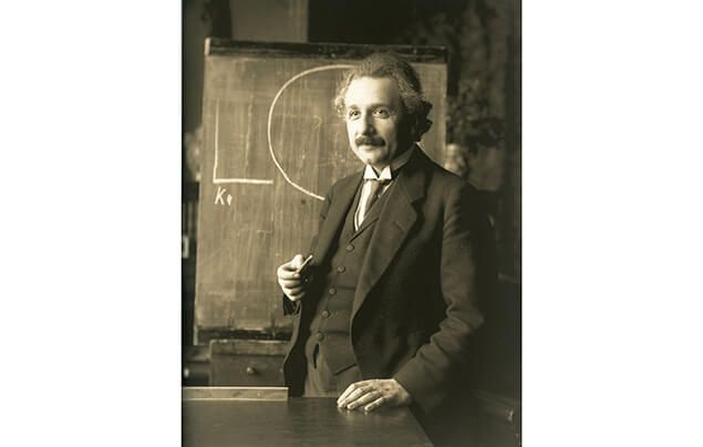 Einstein stands in front of a chalkboard. He is a middle-aged man, with long neat hair and a mustache. He is dressed smartly in a suit jacket and tie.