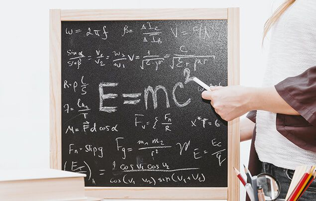 a chalkboard with lots of different mathematical equations on it. one larger equation is in the centre, it reads E = m c-squared. A white hand holding a piece of chalk is pointing to this equation