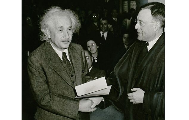 Albert Einstein facts | Albert shakes hands with a tall white man, who is handing him a piece of paper. They are both formally dressed in suits. Albert's hair is long and grey.