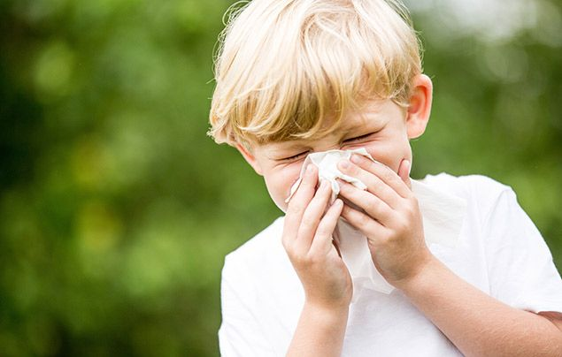 What is coronavirus: boy sneezing into tissue