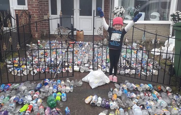 Rayer stands in front of hundreds of plastic bottles laid out on the floor.