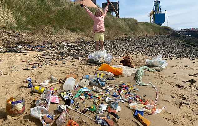 Rayer stands behind lots of plastic picked up on a beach clean