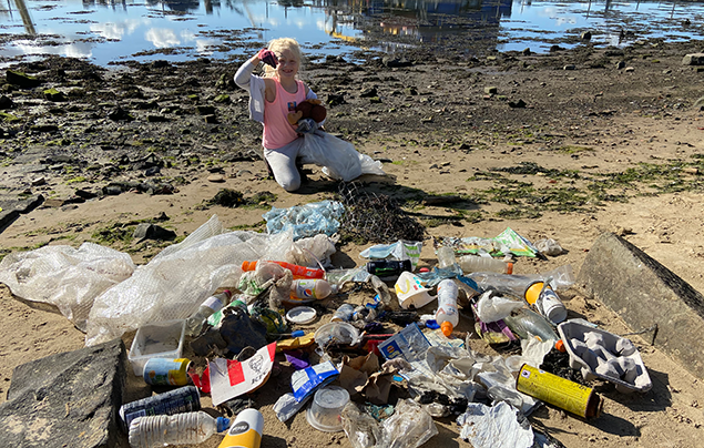 Rayer sits on the beach in front of a large pile of rubbish