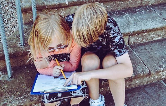 two blond children, a boy and a girl, sit together. they are filling in a clipboard and clearly working together.