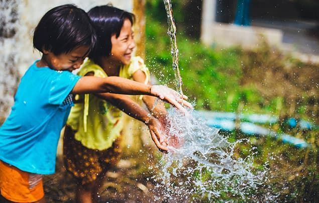 Two young girls play in clean water that spills down from a tap