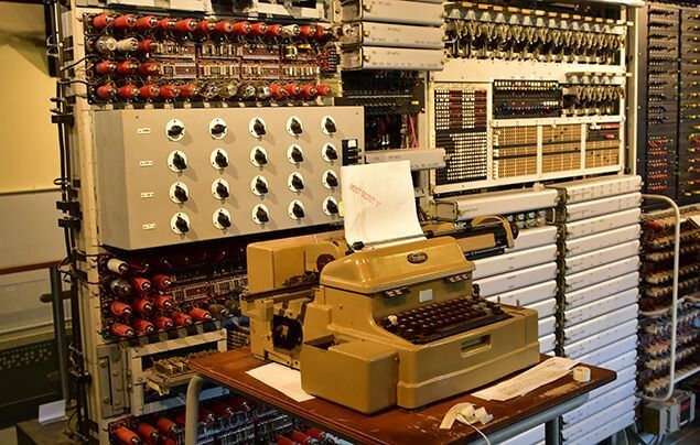 alan turing facts | a photograph of one of the oldest computers, which looks like a typewriter surrounded by machinery boxes