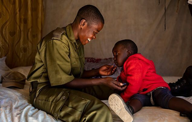 a female wildlife ranger wearing khakis smiles down at a young child wearing a red hoody