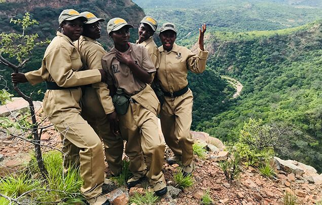 female wildlife rangers stand in a group. they are smiling and wearing khakis