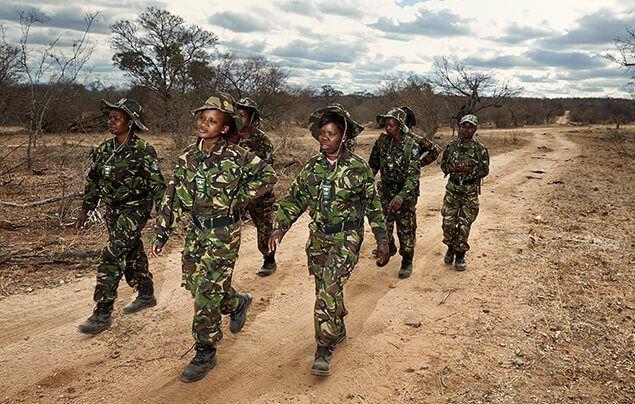 a team of female wildlife rangers march forward in rows