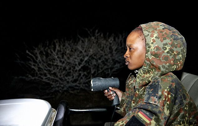 a female wildlife ranger scans the night using a torch. it's night time, the bush behind her is dark, she's sitting in an open top jeep wearing khakis.