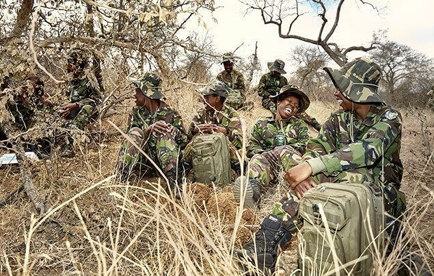 female wildlife rangers sit together on the ground of the savannah, chatting and laughing