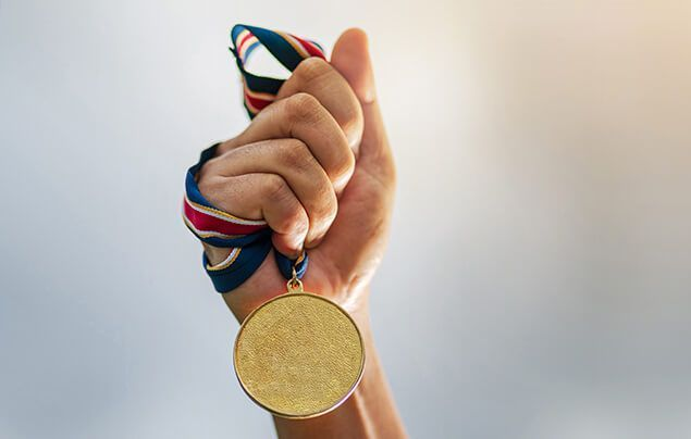 Facts about the olympics | a hand holds a gold medal