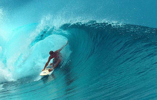 facts about the olympics | a surfer just emerges along a wave, as it breaks behind them