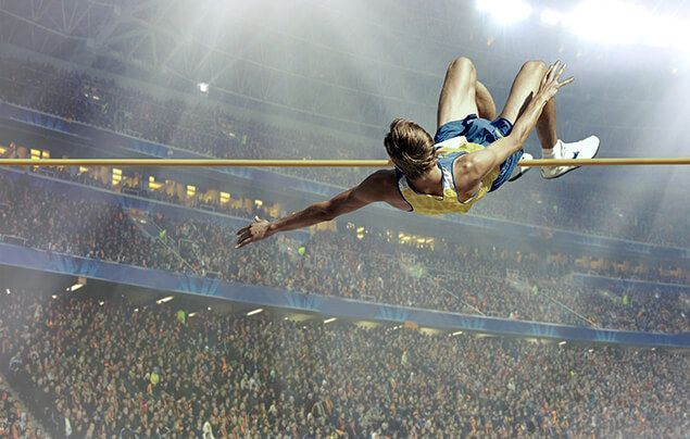 a man just crosses the bar of a high jump. behind him, a crowd of thousands cheers from a stadium