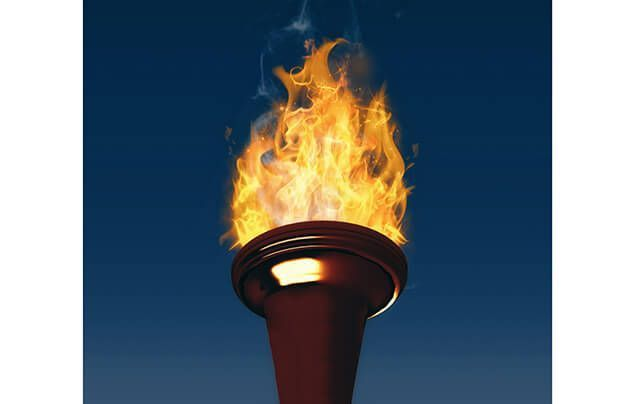 facts about the olympics | a torch burns against the night sky