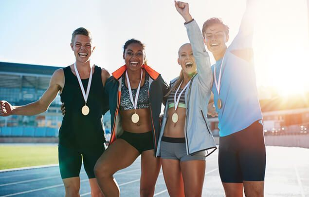 four young athletes, each wearing a gold medal, stand together smiling
