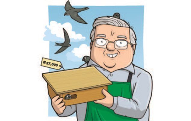 swift nest boxes | john holds up his 27000th nest box as swifts fly past behind him
