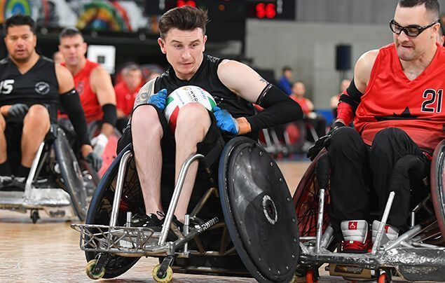 paralympic athlete cody wheels away from an opponent, the ball clasped in his lap