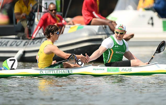 paralympic athlete dylan sits in his canoe on a lake. he slaps palms with a teammate and looks pleased.