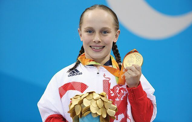 Ellie smiles at the camera, holding up her shiny gold medal