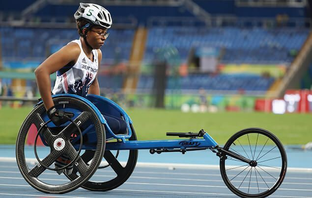 paralympic athlete karé looks focused as she sits in her racing wheelchair, which has two wheels beneath her and one out in front.