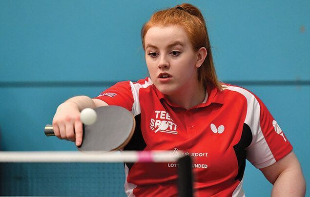 Megan looks focused as she stretches to hit a small table tennis ball with her paddle
