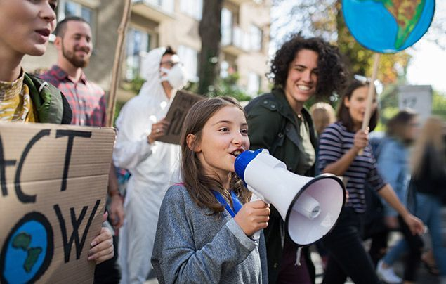 COP26 glasgow | a young girl holds a megaphone. she is surrounded by adults holding colourful signs campaigning to protect the Earth.